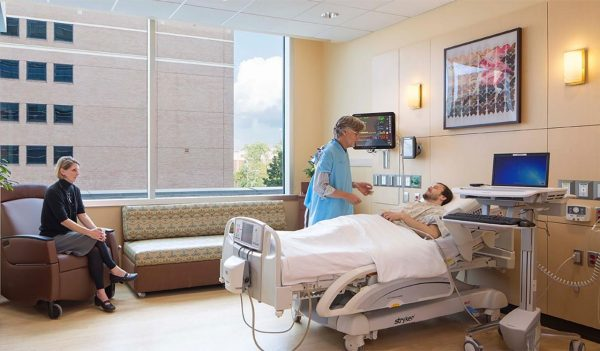 A person in a hospital bed with a nurse and visitor