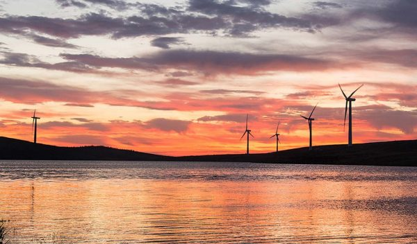 Wind turbines with a lake in front at sunset