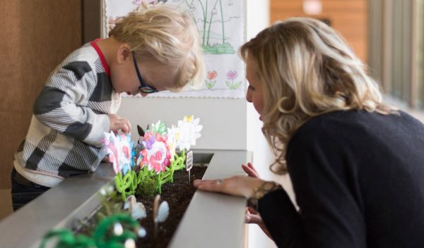 A woman with a child looking at plants in a classroom
