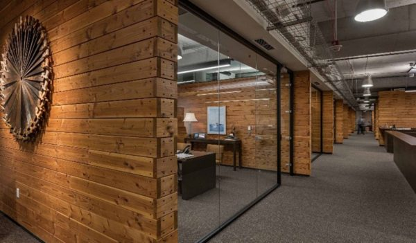 Darker finished wooden walls in office interior with lower lighting levels at Weyerhaeuser Corporate Offices Seattle.