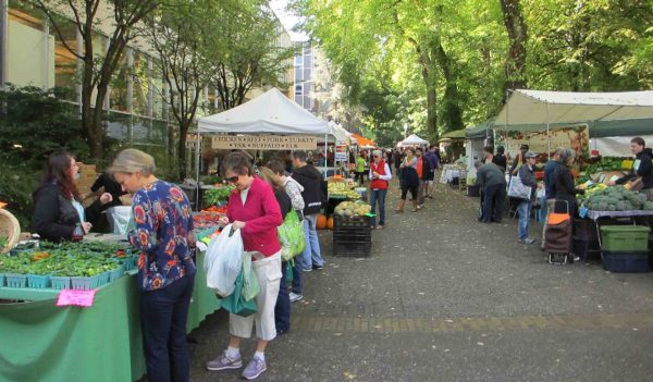 Vendors and shoppers at a farmer's market.