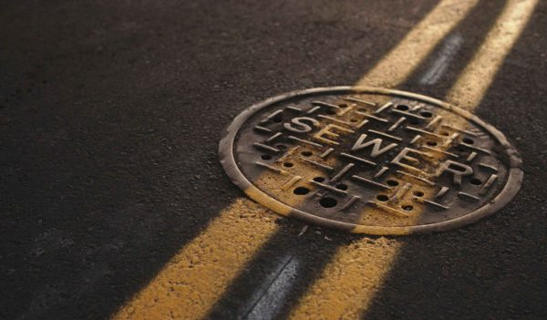 Sewer manhole cover on highway with yellow lines painted overtop.