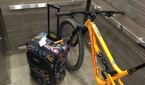 Bike and suitcase in an elevator.