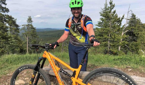 Adam Baxter smiling with his bike next to a trail in Calgary.