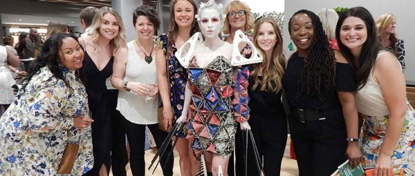 Stantec interior designer and MERGE Fashion Show model Rebecca Keehner is surrounded by other team members on the night of a runway show.