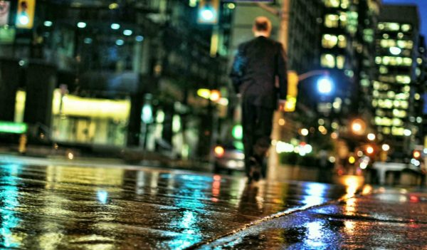 Man walking in the city in the rain at night
