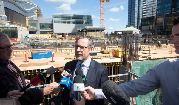 Keith Shillington, senior vice president, talking with reporters in front of Stantec Tower construction site.