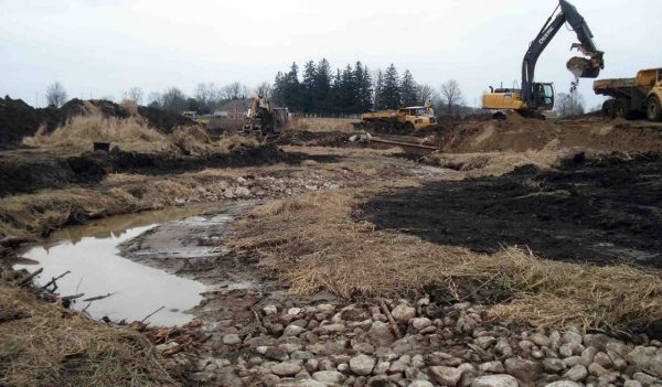 Excavators working next to stream in need of rehabilitation.