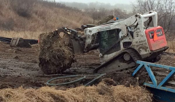 Skidsteer moving large piece of earth with forks.