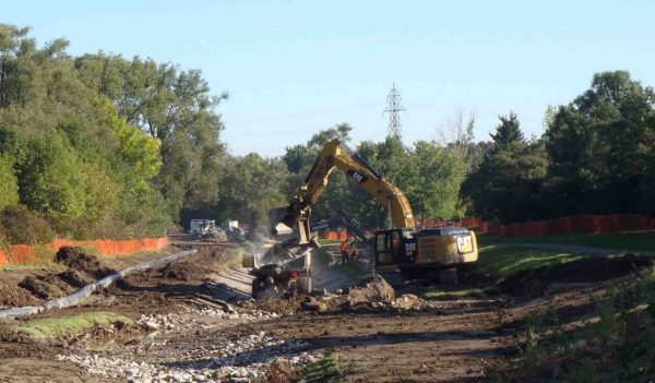 Excavator working next to gravity bypass pipe installed at stream restoration project.