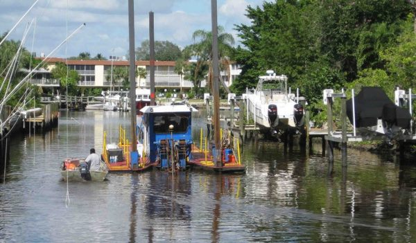 hydraulic dredge removes sediments within a residential canal
