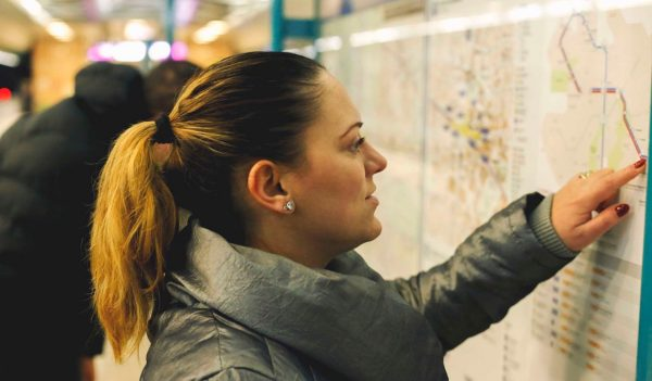 Tourist girl in metro, looking at the map