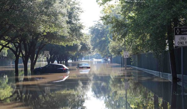 Cars floating down a flooded street in Houston, Texas.