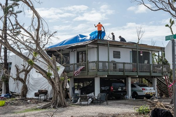 Big Pine Key, FL - Workers begin repairs on the roof of this house which was damaged during Hurricane Irma