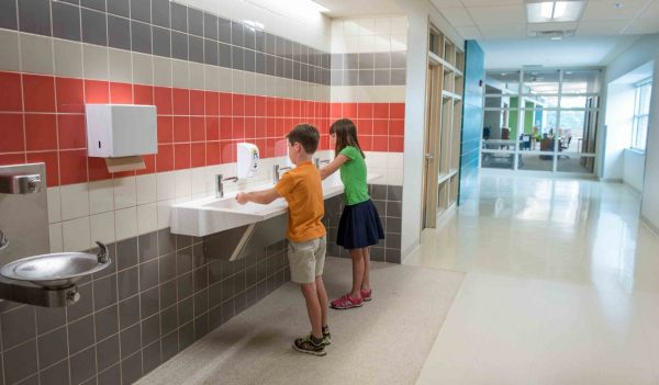 Students washing hands in a corridor hand washing station