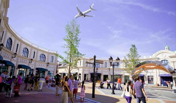Plane flying over outdoor shopping area