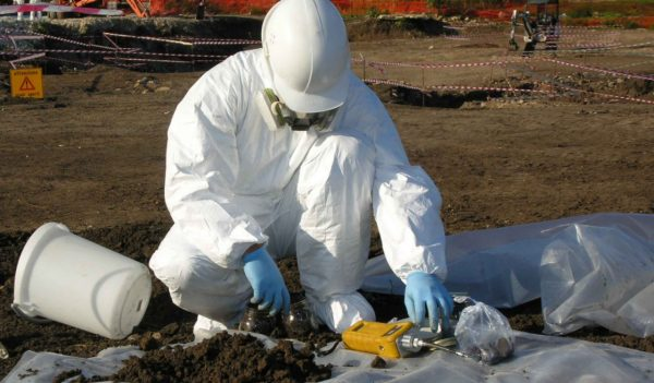 worker in white suit inspecting dirt