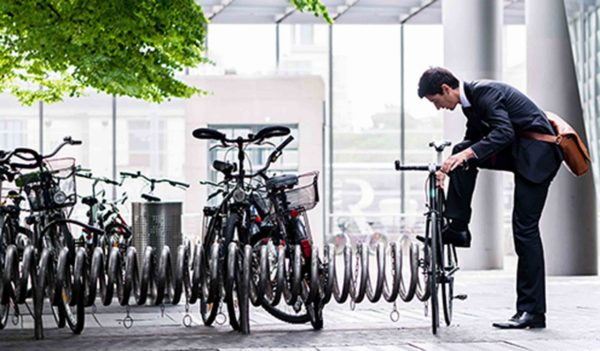 Businessman parking his bicycle in town at a bicycle rack after commuting to work