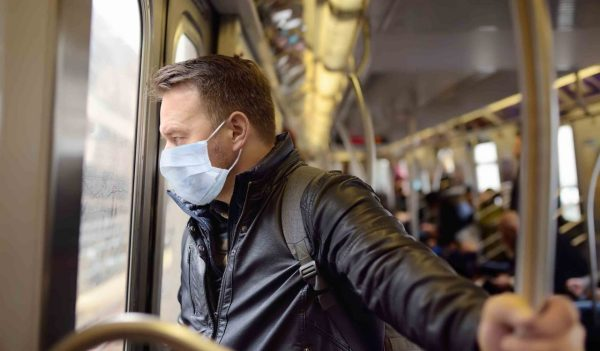 Mature man wearing disposable medical face mask in car of the subway in New York during coronavirus outbreak. Safety in a public place while epidemic of covid-19.