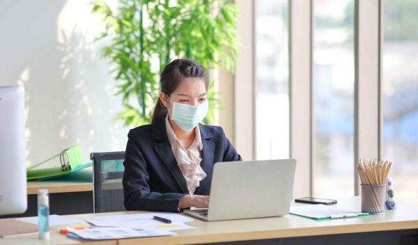 Female employee wearing medical face mask while working alone because of social distancing policy in the business office during coronavirus or covid-19 outbreak pandemic situation