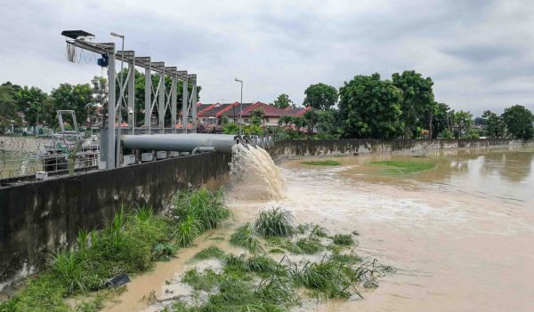 Rain water being extracted pumped into river from flood storm retention pond after rain.  Public flood management system in Malaysia.