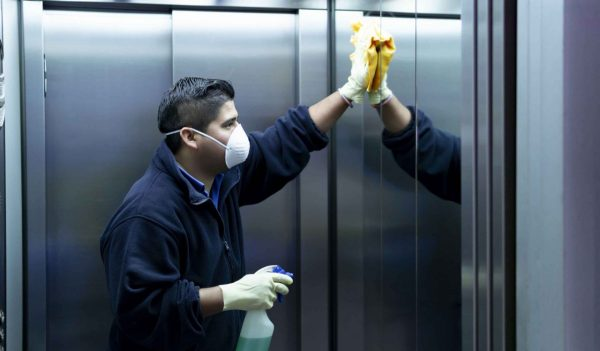 coronavirus. cleaning staff disinfecting elevator to avoid contagion