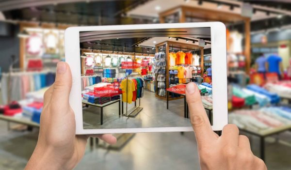 Augmented reality marketing concept. Hand holding digital tablet smart phone use AR application to check special sale price in retail fashion shop mall