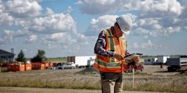 Man standing holding a tablet on a construction site