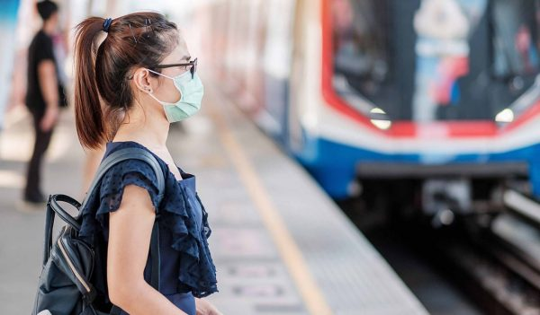 young Asian woman wearing Surgical face mask against Novel coronavirus or Corona Virus Disease (Covid-19) at public train station. Hygiene, Healthcare and infection concept