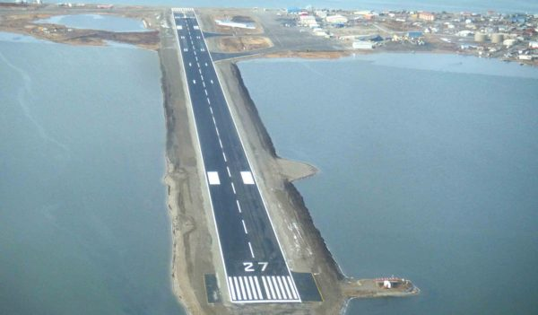 Aerial view of runway extending into the water