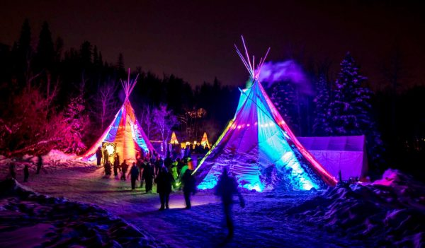 Winter festival at night with teepees lit up